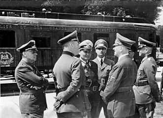 Compiègne Wagon - Left to right: Joachim von Ribbentrop, Wilhelm Keitel, Hermann Göring, Rudolf Hess, Adolf Hitler, Erich Raeder partially obscured and Walther von Brauchitsch in front of the Armistice carriage