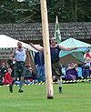 Photo d'un homme lançant un tronc d'arbre devant lui pour l'épreuve du Caber.