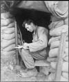 Catching up on his letters to the folks at home during a break in action against the Chinese Communist forces along... - NARA - 531419.tif
