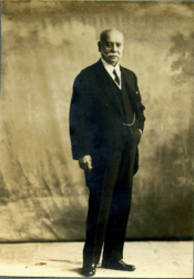 Full-length sepia portrait of distinguished gentleman with sideburns, wearing a 3-piece suit; body slight left-tilt
