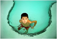 A boy in a shallow children's pool.