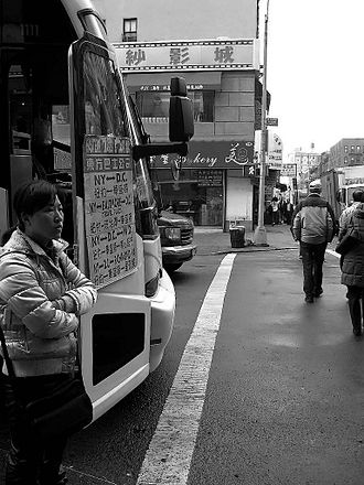 East Broadway (Manhattan) - Bus ticket saleswoman at the corner of East Broadway and Forsyth Street in the Little Fuzhou neighborhood within Manhattan's Chinatown.
