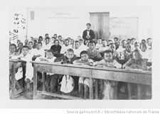 Children tightly packed on benches at desks in a crowded classroom