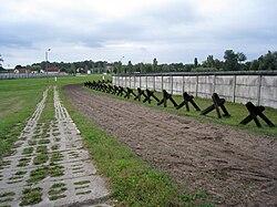 Een strook kale omgeploegde aarde geflankeerd door een betonnen weg aan de ene kant en een rij barricades en een hek aan de andere kant, met gebouwen in de verre achtergrond.