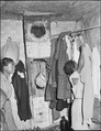 Daughter of Lawson Mayo hanging up clothing. The house was in bad repair when they moved in, nothing has been... - NARA - 540967.tif