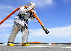 Defense.gov News Photo 110927-N-WJ771-108 - U.S. Navy Petty Officer 2nd Class Joshua B. Cary carries a charged fire hose across the flight deck of the amphibious transport dock ship USS Denver.jpg