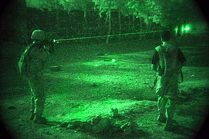 Night combat - As seen through a night-vision device, United States Army Sergeant Andrew Burch and an Afghan soldier scan a tree line for militants during Operation Champion Sword.