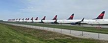 Многие выстроились в линию самолетов с логотипом Delta Air Lines на хвосте, припаркованных на тротуаре за забором.
