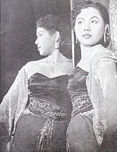 A black and white photograph of a woman in front of a mirror.