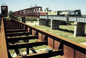 Great Northern Railway (Mt Isa line) - QR loco 1501 hauls a special train across the 1960s era Burdekin River bridge, September 1989. The original 1882, now disused bridge is in the foreground.