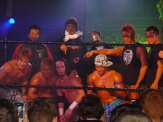 Neville (wrestler) - Pac (bottom centre) posing with various Dragon Gate wrestlers