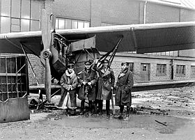 Four men in military uniforms with overcoats, standing next to a biplane parked in front of a building