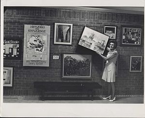 Edina Library - Dorothy Dunn, Librarian, shows off Edina Library's art lending collection, 1970s.