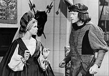 A black-and-white photograph of two people, a woman on the left and a man on the right, both standing and looking at each other while wearing poofy hats