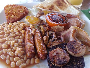 British cuisine - A full English breakfast with fried egg, sausage, white and black pudding, bacon, mushrooms, baked beans, hash browns, toast, and half a tomato