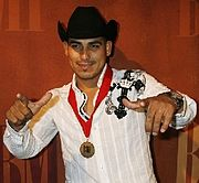 A dark man with black hat, white shirt, raising both hands, with a medal with red ribbon around his neck and legend BMI in the front.