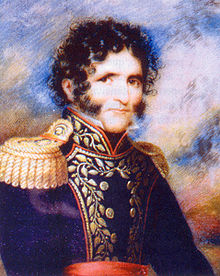 Head and shoulders of curly haired young man with bushy sideburns and moustache, dressed in 19th-century clothes.