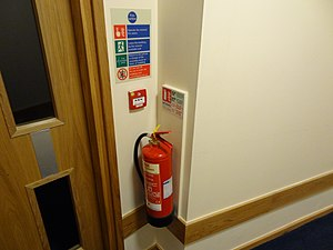 Fire extinguisher - A British fire extinguisher with ID sign, call point and fire action sign