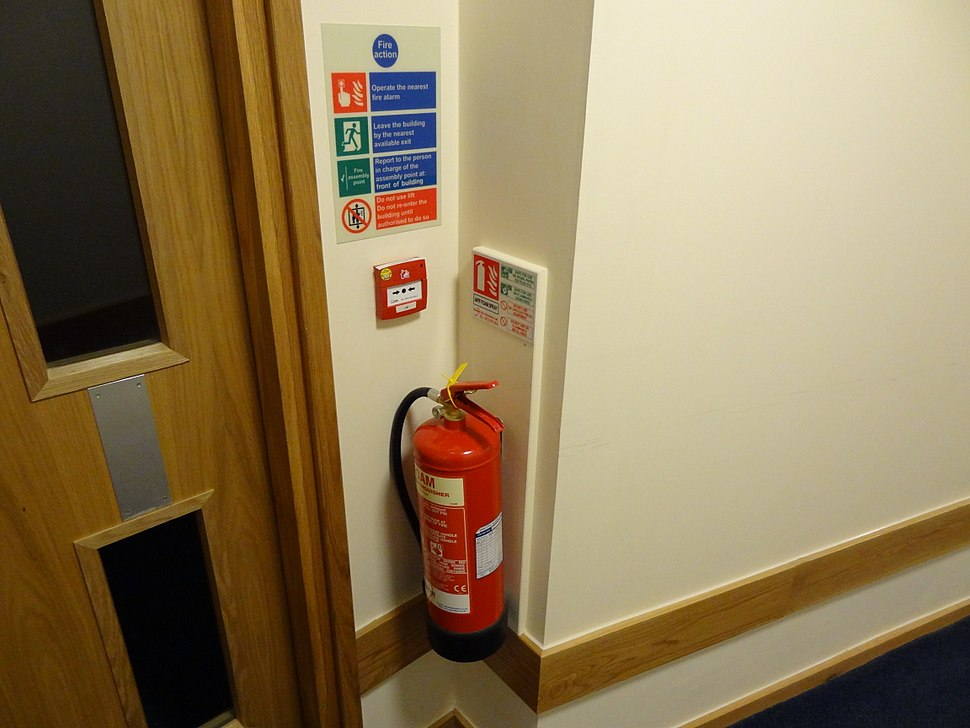 Fire extinguisher with ID sign, call point and fire action sign
