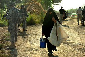 An Iraqi woman walks between Soldiers as they ...