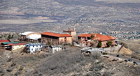 A cluster of buildings with orange slate roofs, seen from a hill above