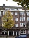 foto van Pand, deel uitmakend van een huizenblok, in een trant die met zijn hoekige en stekelige detaillering het begin van de 'Amsterdamse School' aankondigt