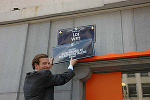Flemish Secession hoax - Geoffroy Coomans de Brachène holding the street sign Rue des contribuables/Belastingsbetalers street (taxpayers' street) in Brussels