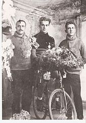 Three men standing next to each other. The man in the middle is sitting on a bicycle with many flowers. The picture is slightly damaged, as if it is an old photograph.
