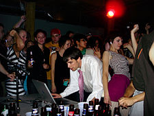 A Caucasian man wearing a tie performs music using a laptop. Several people dance around him.
