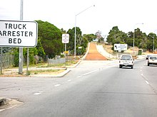 View of gavel-filled lane leaving the side of the road and then rising up a slope. Signs either side of it read 'TRUCK ARRESTOR BED'.
