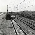 HUA-168970-Gezicht op de spoorlijn nabij Lisse, met zig-zag dwarsliggers en een paserend diesel-electrisch treinstel DE 4 (RAm, T.E.E.) van de N.S.-S.B.B.jpg