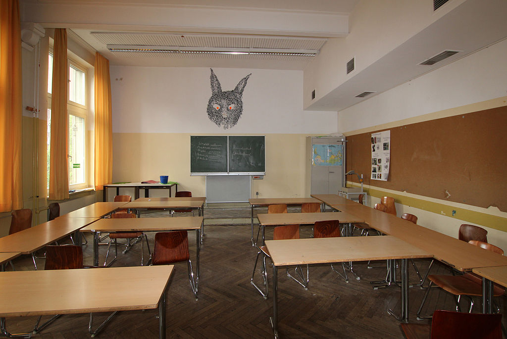 leerer Klassenraum mit einem an die Wand gemalten, sehr großen Hasenkopf mit orangenefarbigen Augen