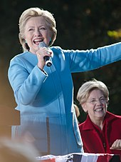 Photograph of Clinton in a light blue suit, holding a microphone and speaking in front of Elizabeth Warren who is seated behind her