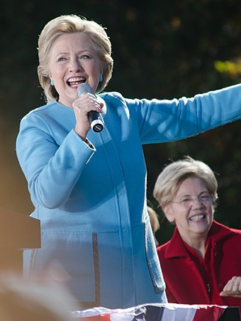 Clinton campaigning for president in Manchester, New Hampshire, in October 2016, with Massachusetts senator Elizabeth Warren (seated) Hillary Clinton Elizabeth Warren Manchester NH October 2016 (1).jpg