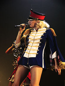 A blonde lady sings into a microphone, which is held in her right hand, in front of a dark blue background. She is wearing a white dress, with yellow-and-white stripes on the arms and white frills on the torso and a black belt around her waist.