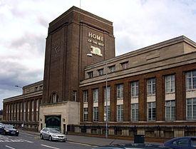 "A long three-storey building made of brown brick. It has large windows and its tall central square tower provides a fourth storey. The side of the tower facing the road has large decorative iron gates at street level, and a simple clock closer to the top. The words ""Home of the Best"", above the stylised lowercase letter 'n' representing Nottinghamshire County Council, are on the other side of the tower that is visible."