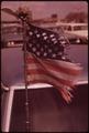 INSPIRING EMBLEMS ON CAR ANTENNA IN ONE OF THE CITY'S CHRONIC TRAFFIC JAMS - NARA - 554361.tif