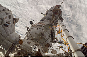 Strela (crane) - Flight Engineer Kononenko photographs commander Volkov operating the manual Strela crane holding him. The commander stands on Pirs and has his back to the Soyuz spacecraft. Zarya is seen to the left and Zvezda across the bottom of the image.