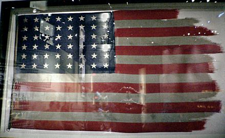 The flags from the first and second flag-raisings are conserved in the National Museum of the Marine Corps; the second flag, pictured here, was damaged by the high winds at the peak of Suribachi (American flags during World War II, had 48 stars, since Alaska and Hawaii were not yet U.S. states) - Raising the Flag on Iwo Jima