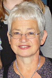 A portrait of a bespectacled, smiling middle-aged woman with short, light grey hair.