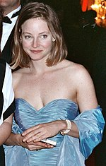 A close up image of a brown-haired woman wearing a blue dress.