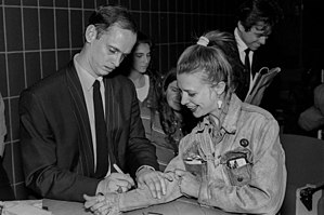 John Waters - John Waters signing a fan's jean jacket sleeve at the Massachusetts College of Art in Boston, 1990.