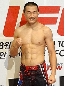 A grinning shirtless South Korean man with a raised clenched fist.
