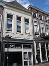foto van Huis met geverfde lijstgevel met lijst met tandlijst en met jongere winkelpui