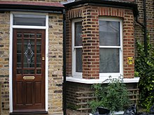 A brown brick building. Visible is a door at left, with a bowfront window at right; various tomato plants are also visible growing in front of the window.