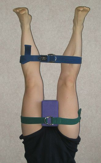 Iyengar Yoga - Legs constrained with belts and a foam block in a therapeutic Iyengar Yoga pose