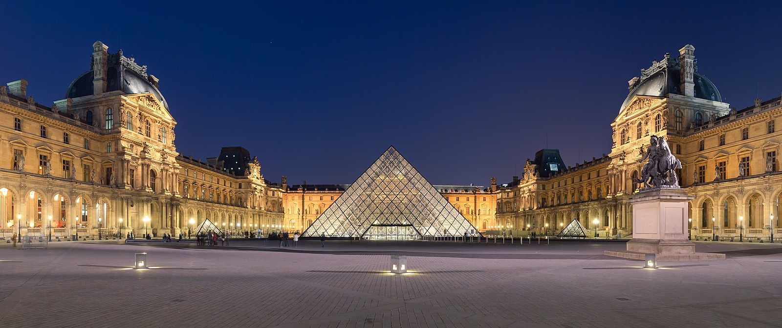 The Louvre Palace and the pyramid (by night) Louvre Museum Wikimedia Commons.jpg