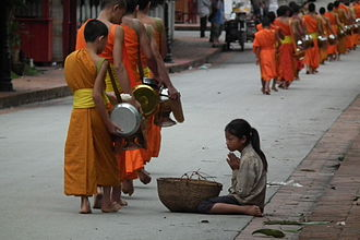A young layperson providing monks with alms Luang Prabang Takuhatsu ruanpaban Tuo Bo DSCF7017.JPG