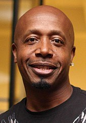A image of a black man with an earring in his left ear. He is smiling and wearing a brown shirt.