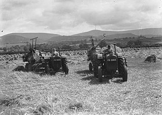 Man and woman harvesting with tractors